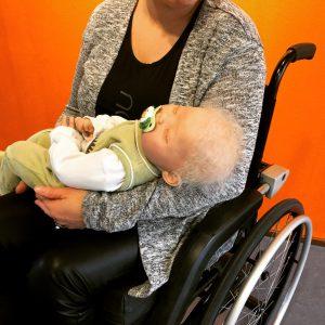 Pyörätuolissa istuva nainen pitää sylissään aidon vauvan näköistä vauvanukkea, jolla on tutti suussaan.