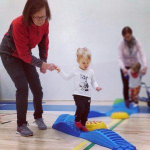 Nainen pitää kädestä pientä tyttöä, joka kulkee tasapainoradalla sinisen vaahtomuovialustan päällä. Taustalla näkyy toinen aikuinen ja lapsi samalla radalla.