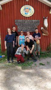 Seitsemän henkilöä ryhmäkuvassa Repoveden kansallispuisto -kyltin alla. Taustalla talon seinä, jossa kyltin lisäksi puusta veistetty kettu.
