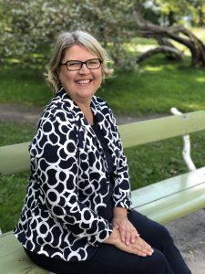 Toiminnanjohtaja Marju Silander istuu puistonpenkille hymyillen.