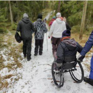 Ryhmä ihmisiä kulkee selin katsojaan lumisella polulla metsässä. Yksi kulkee sauvaan ja toiseen ihmiseen tukeutuen, Etualalla ihminen pyörätuolissa.