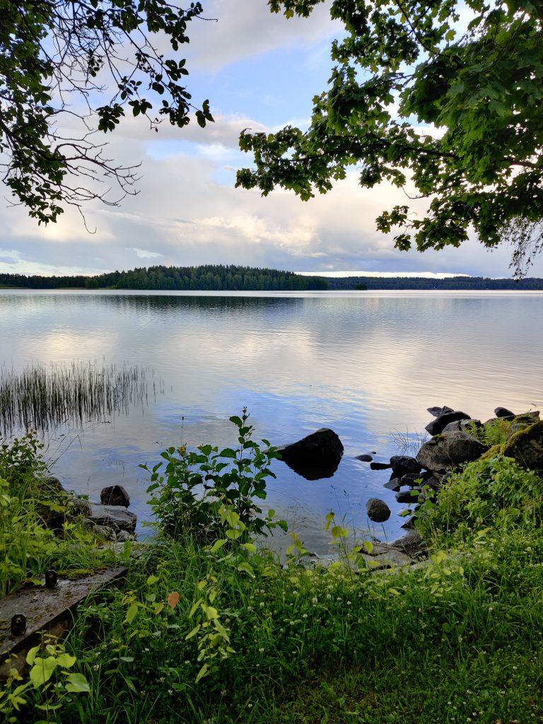 Kaunis järvimaisema Moijalasta. Tyyni järvi, horisontissa näkyy metsää.