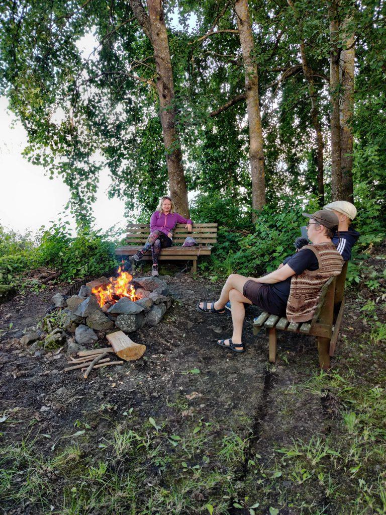 Kolme ihmistä istuu penkeillä nuotion äärellä puiden katveessa. Taustalla järvi.
