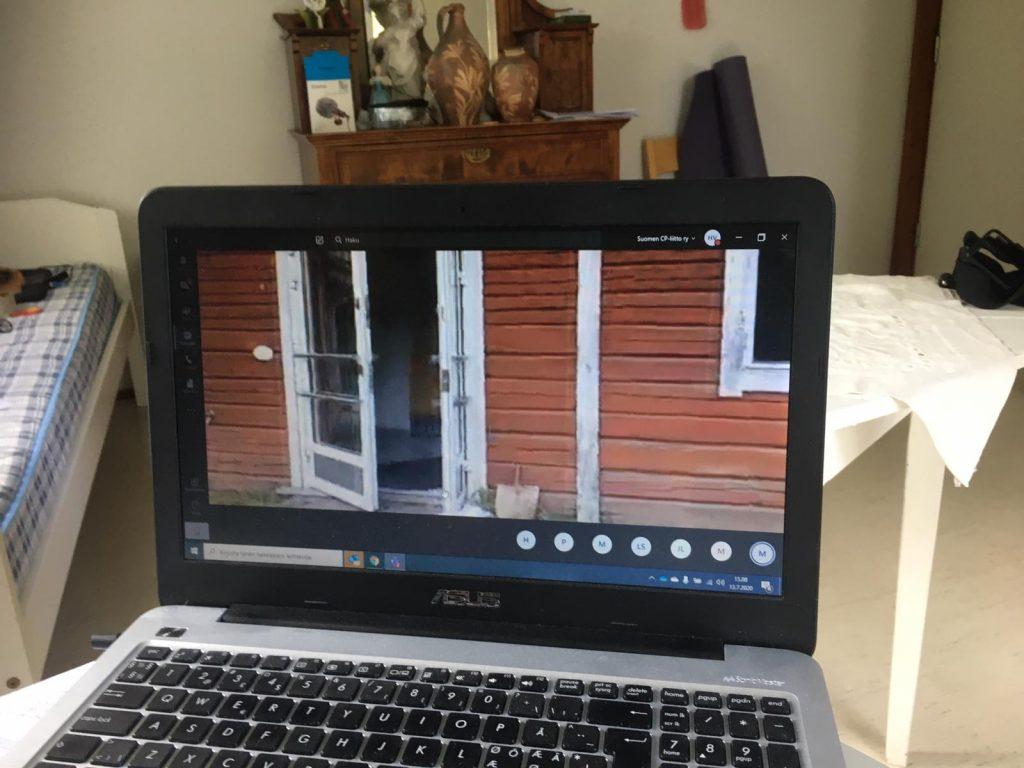Kannettavan tietokoneen näytöllä kuva punamultaiseisesta hirsitalosta, jonka valkoisella maalattu ovi on raollaan.