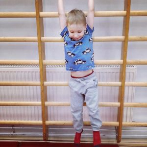 Lapsi roikkuu nojapuilla ja katsoo alaspäin.