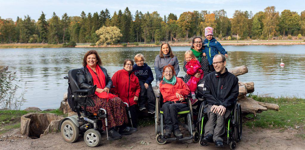 Yhdeksän ihmistä ryhmäkuvassa meren rannalla, taustalla metsää. Eturivissä nainen ja mies pyörätuoleissa ja nainen sähköpyörätuolissa. Takarivissä äiti kahden leikki-ikäisen lapsen kanssa.