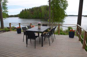 Terassinäkymä, jossa pöytä ja kuusi tuolia. Taustalla järvimaisema, veden taustalla puita. Terassilla ruukuissa pelargoneja.