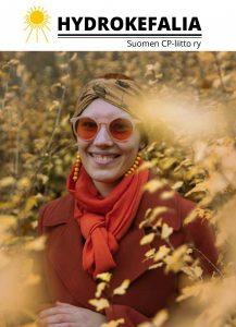 Oranssin syksyisen pensaan keskellä hymyilevä nuori nainen, jolla punertava villakangastakki, oranssi hyivi ja oransseista puupalloista tehdyt korvakorut. Naisella päässä huivi ja oranssisävyiset silmälasit.