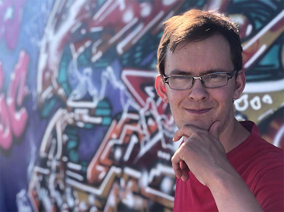Silmälasipäinen mies graffitiseinän edessä katsoo kameraan tiukka ilme katsoillaan ja pitää sormiaan leuallaan.