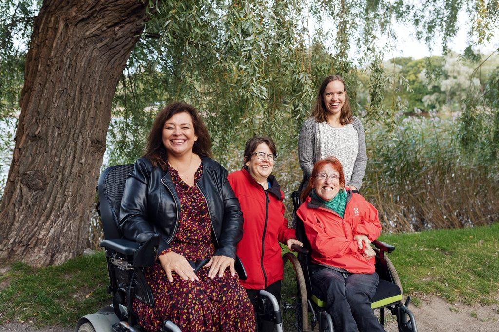 Neljä naista ulkona hopeapajun katveessa. Yksi naisista istuu sähköpyörätuolissa, toinen manuaalipyörätuolissa. Toiset kaksi seisovat. Kaikki hymyilevät.