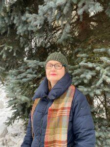 Anne-Mari Raassinan puolimuotokuva. Silmälasipäiselä Raassinalla vihreä pipo päässä, sininen toppatakki ja ruudullinen kaulaliina. Hän seisoo ulkona suuren kuusen edessä.