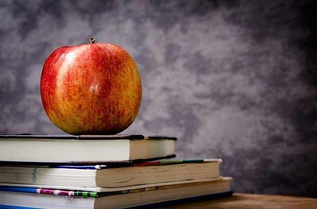 Kirjapinon päällä on omena.