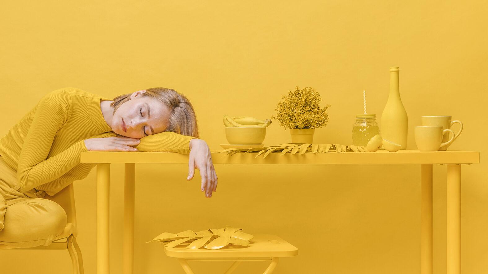 Keltaisiin vaatteisiin pukeutunut nainen istuu tuolilla keltaisen pöydän vieressä. Naisen kädet nojaavat pöytään ja hän lepää päätä vasten kättään silmät kiinni. Pöydällä keltaisia tavaroita.