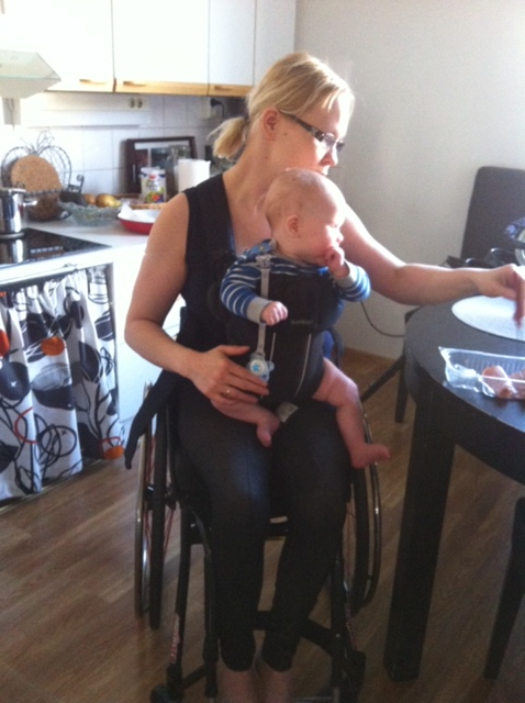 Pyörätuolissa istuva nainen, keittiössä. Naisella on vauva rintarepussa.