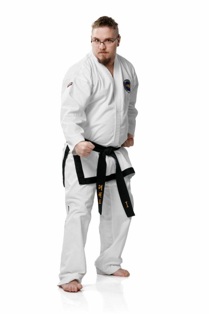 Roope Huuhtanen seisoo valkoinen taekwondo-asu ja musta vyö yllään kasvotusten katsojaan päin kädet nyrkissä vyötärön korkeudella.