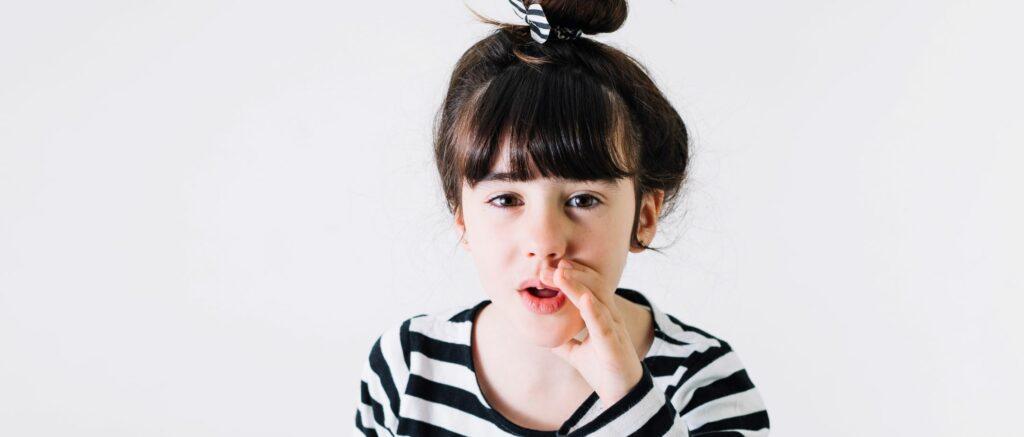 Tummahiuksinen lapsi pitää kättä suun vieressä kuin kuiskatakseen jotain.