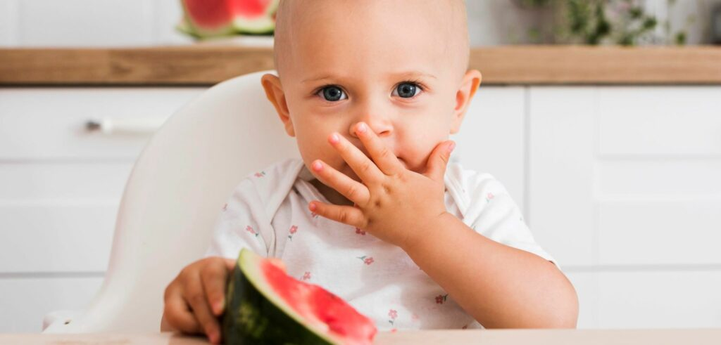 Vauva syö sormin vesimelonia.