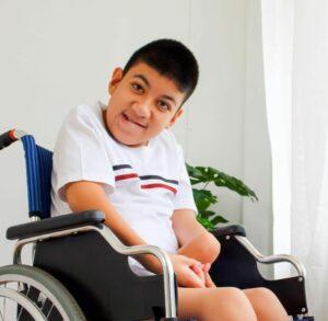 pyörätuolissa istuva poika, jonka toinen käsi on jäykistynyt ranteesta osoittamaan vatsaa kohti. Toisen käden sormet ovat puristuneet yhteen.