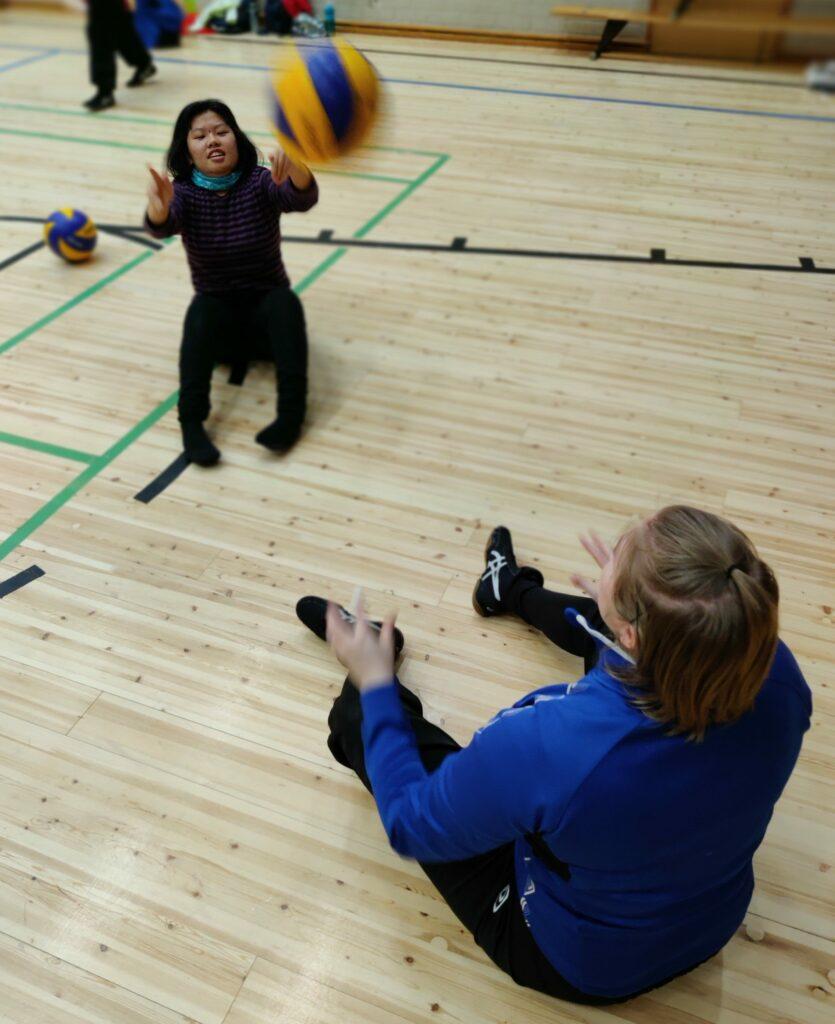 kaksi naista istuu liikuntasalin parkettilattialla ja pelaa lentopalloa. Pallo lentää ilmassa naisten välissä.