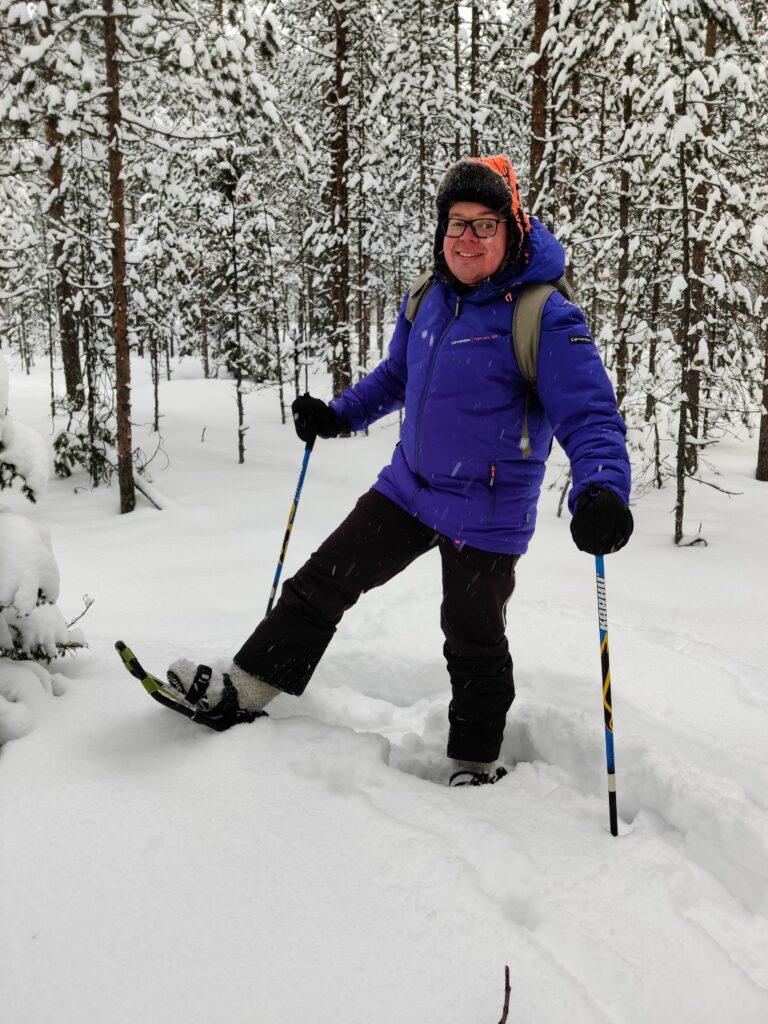 Hyvyilevä mies seisoo lumihangessa metsän keskellä. Miehellä on lämpimät vaatteet, lumikengät ja sauvat. .