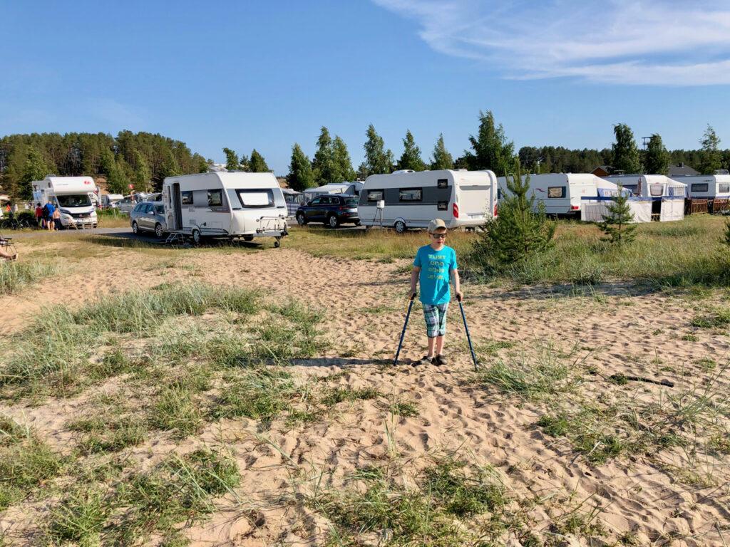 11-vuotias Eelis Salo kävelee keppien avulla hiekalla, jossa kasvaa ruohikkoa. Taustalla useita asuntovaunuja ja asuntoautoja.