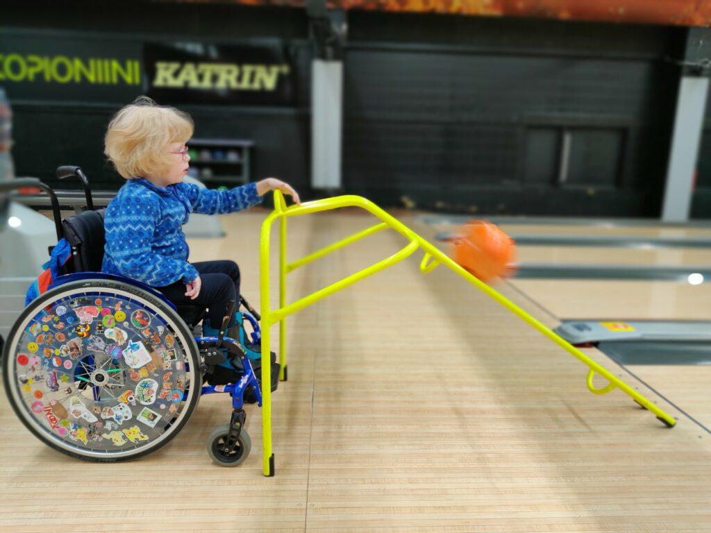 vaaleahiuksinen tyttö istuu pyörätuolissa keilahallssa. Tyttö työntää kädellä keilapallon radalle apukourun avulla.