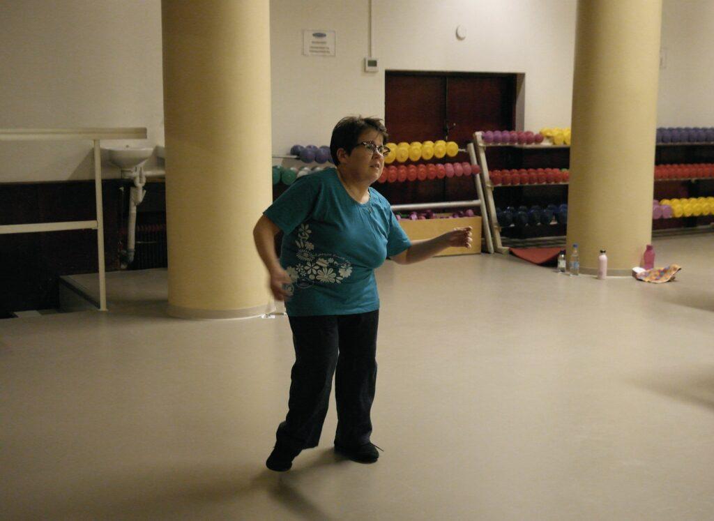 Nainen tanssii jumppasalissa. Huoneessa hämärä valaistus ja taustalla värikkäitä käsipainoja la juomapulloja.