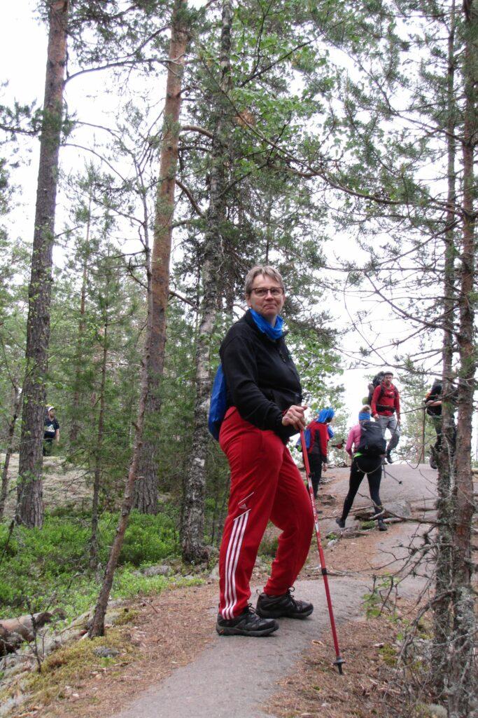 Hymyilevä nainen seisoo metsässä kalliolla kulkevalla polulla. Kädessä naisella on sauvakävely-sauvat. Taustalla on muita kävelijöitä.