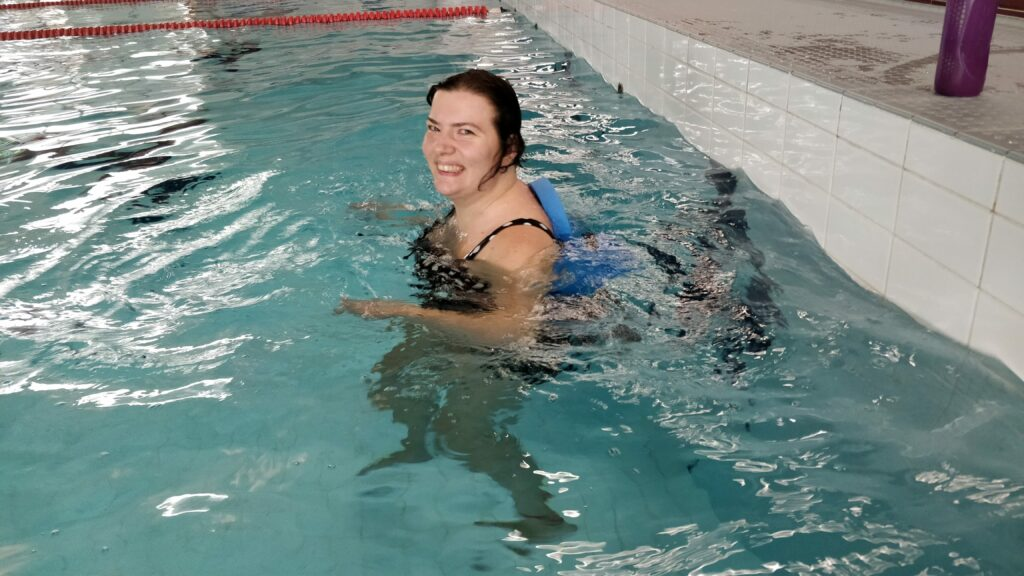 Hyvyilevä nainen on uima-altaassa vesijuoksuvyö vyötäröllä.