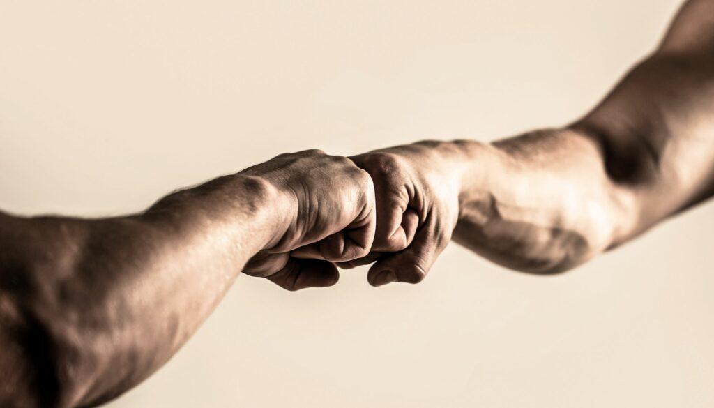 Miehet lyövät nyrkkejä yhteen, mustavalkoinen kuva
