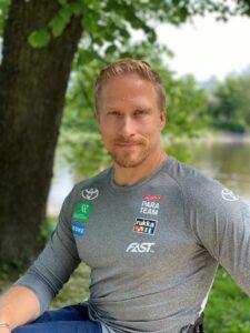 Paraurheilija Leo-Pekka Tähti katsoo kameraan hymyilleen. Lyhyet vaalea tukka, vaalea parta ja viikset. Yllä harmaa paita jossa sponsoreiden logoja. Taustalla vehreä puu ja vettä.