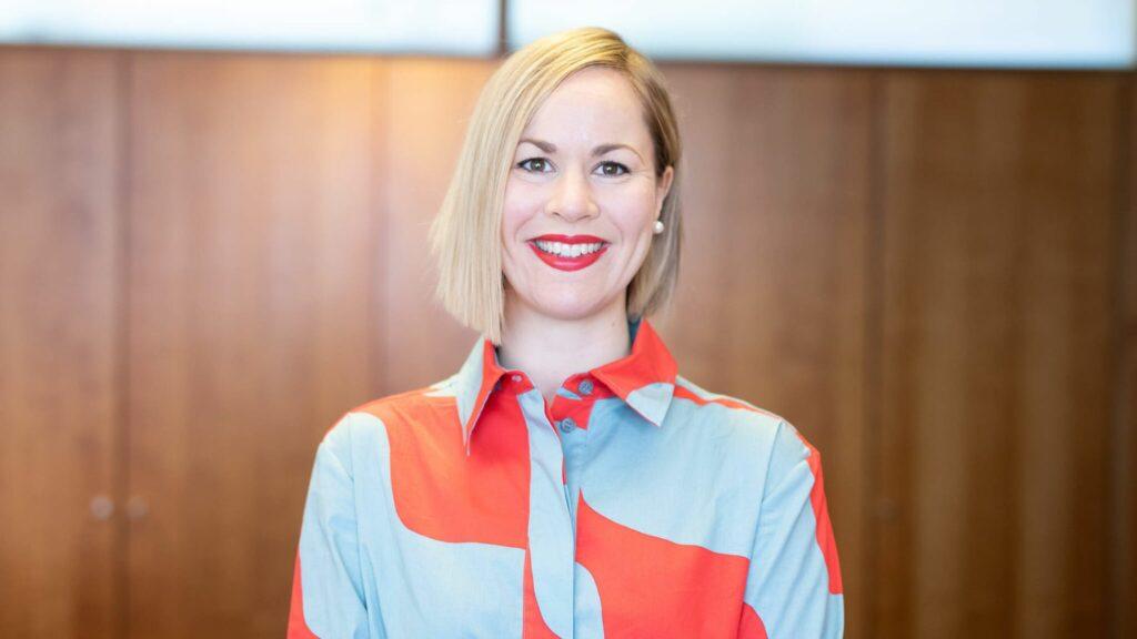 Ministeri Hanna Sarkkinen hymyilee rintakuvassa. Polkkatukka, punainen huulipuna, vaaleansini-punainen marimekon kauluspaita.
