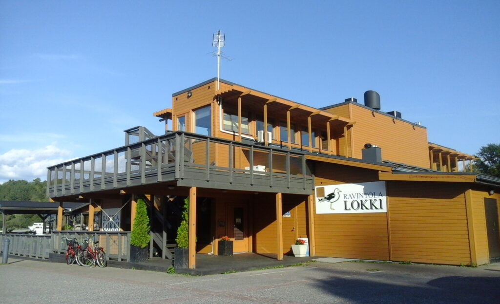 Kuvassa näkyy ravintola Lokki Lahdessa Vesijärven rannalla. Tosin vettä ei kuvassa näy, mutta lähes pilvetön sininen taivas. Etualalla on asfalttia. Lokissa on lautaverhous ja eri ruskean sävyjä seinissä ja tolpissa. Seinällä iso kyltti valkoinen kyltti, jossa lukee mustalla ravintola Lokki ja on lokin kuva.