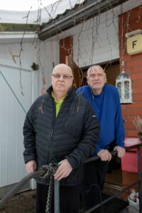 Kaksi miestä seisovat punatiilisen talon edustalla ja nojaavat kaiteeseen.